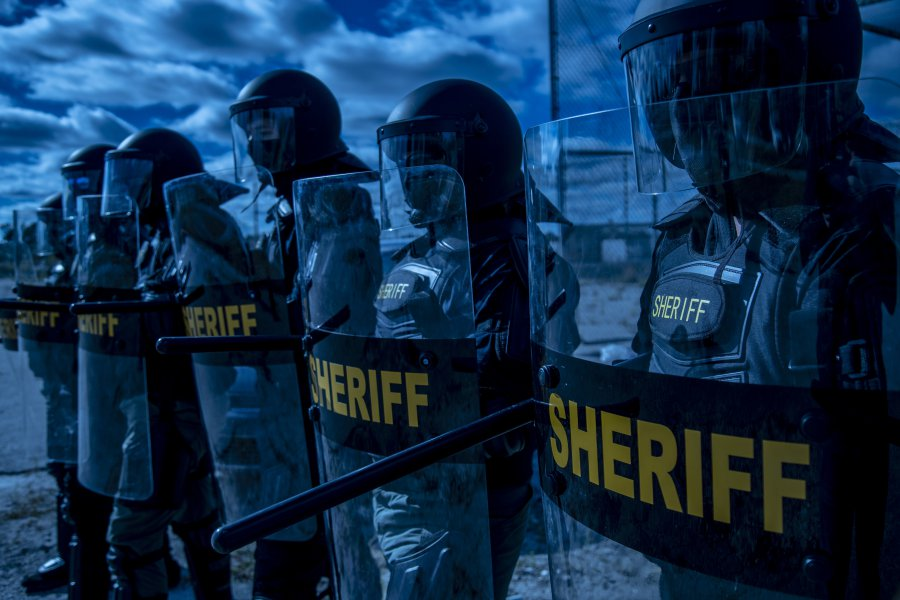 10HG1. The Evolution, Design, and Uses of Riot Shields. Police lined up to protect. Riot